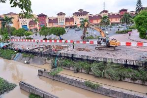 Clean-up: Workmen seen de-watering the LRT construction site in front of the flood-hit surface carpark at IOI Mall Puchong. ( The Star)