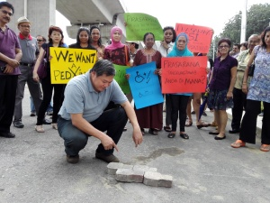 Tony Yew demonstrates with bricks the solution to the problem posed by the SS18 LRT station at the recent residents' protest near the station. – The Malaysian Insider pic by Robin Augustin, October 30, 2015. - See more at: http://www.themalaysianinsider.com/citynews/greater-kl/article/ss18-residents-protest-barrier-to-ss14-posed-by-upcoming-lrt-station#sthash.pkJM3d1p.dpuf